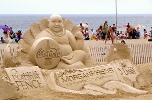 sculpture coca-cola en sable sur une plage